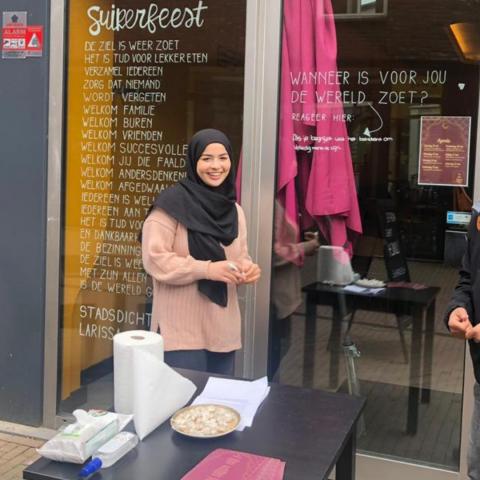 foto van een vrouw met een lichtroze trui en een zwarte hoofddoek. Ze staat achter een tafel met een keukenrol en hapjes erop en voor een etalage waar op het raam het gedicht Suikerfeest staat van Larissa Verhoeff.
